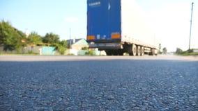 De vrachtwagen drijft langs een asfaltweg De vage auto berijdt bij de weg in de de zomeravond Sluit omhoog langzame motie stock video