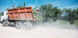 De vrachtwagen is drijven, gevolgd door een wolk van stof stock afbeelding