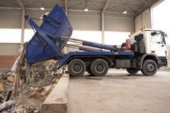 De vrachtwagen dumpt afval aan de verbrandingsoven, gat waar de grote greep het vuilnis neemt en zette het in brand Al afval word stock foto