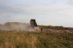 De vrachtwagen dumpt puin van het lichaam van bouwpuin op het gebied overtreedt de wetskwaad milieumensen het letten op stock afbeeldingen