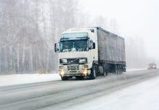 De vrachtwagen gaat op de winterweg Stock Fotografie