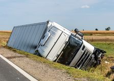 De vrachtwagen ligt in een zijsloot na het verkeersongeval stock afbeeldingen