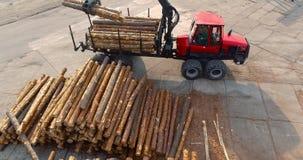 De vrachtwagen met een kraan laadt logboeken, die logboeken met een manipulator laden Een vrachtwagen met logboeken bij een zaagm stock videobeelden