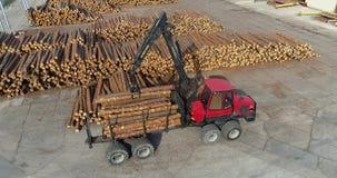 De vrachtwagen met een kraan laadt logboeken, die logboeken met een manipulator laden stock videobeelden
