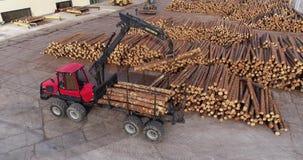 De vrachtwagen met een kraan laadt logboeken, die logboeken met een manipulator laden Een vrachtwagen met logboeken bij een zaagm stock video