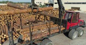 De vrachtwagen met een kraan laadt logboeken, die logboeken met een manipulator laden stock footage