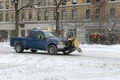 De vrachtwagen met ploeg maakt sneeuw op de straat schoon, de Stad van New York Stock Fotografie