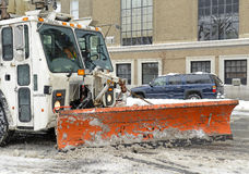 De vrachtwagen met ploeg maakt sneeuw op de straat schoon, de Stad van New York Stock Afbeeldingen