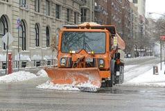 De vrachtwagen met ploeg maakt sneeuw op de straat schoon, de Stad van New York Stock Foto