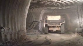 De vrachtwagen van de achtereindmening drijft in tunnel en de arbeider volgt stock videobeelden