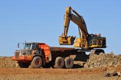 De vrachtwagen van de graafwerktuiglading in mijnsteengroeve stock afbeeldingen