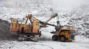 De vrachtwagen van de stortplaats die met een graafwerktuig wordt geladen stock afbeelding