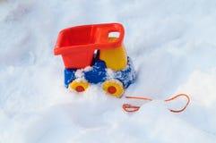 De vrachtwagen van het stuk speelgoed in sneeuw Stock Afbeeldingen