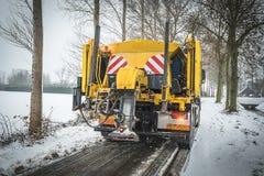 De vrachtwagen van de de winterdienst het uitspreiden zout op weg stock foto