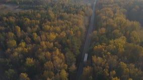 De vrachtwagenauto die van de hommelmening zich op wegweg door de herfstbos bewegen stock footage