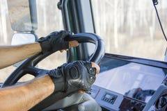 De vrachtwagenchauffeur houdt drijf wiel met beide handen Royalty-vrije Stock Afbeeldingen