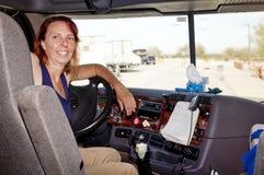 De Vrachtwagenchauffeur van de vrouw bij het Wiel Stock Foto's