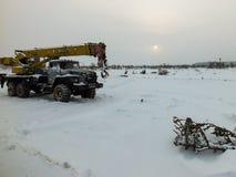 De vrachtwagenkraan in de sneeuw op het gebied Royalty-vrije Stock Afbeeldingen