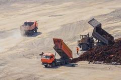 De vrachtwagens bij de bodem van de kuil maken de grond leeg stock afbeeldingen