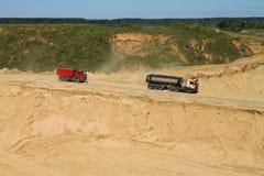 De vrachtwagens dalen in een kuil achter zand Stock Foto