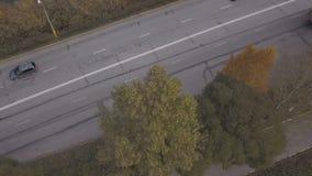 De vrachtwagens en de auto's die van de hommelmening zich op wegweg bewegen op achtergrond de herfstaard stock videobeelden