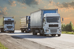 De vrachtwagens gaat op de weg Stock Foto's