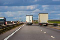De vrachtwagens gaat op de weg Stock Afbeelding