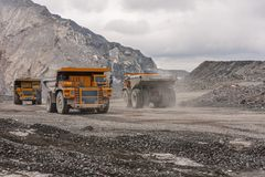 De vrachtwagens van de Gigatstortplaats werken in de mijn voor de productie van apatite in de het gebied van Moermansk dragende r royalty-vrije stock afbeeldingen
