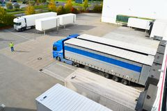 De vrachtwagens worden geladen met goederen bij het depot in een scheepvaartmaatschappij royalty-vrije stock foto's