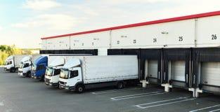 De vrachtwagens worden geladen met goederen bij het depot in een scheepvaartmaatschappij stock fotografie