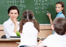 De vragenleerlingen van de leraar bij wiskunde Stock Foto's