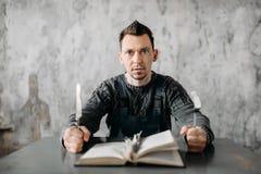 De vreemde buitenissige mens eet de bladen van het boek royalty-vrije stock foto's