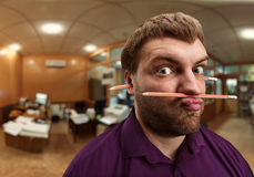 De vreemde mens houdt potlood met zijn neus en lippen stock foto's
