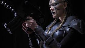 De vreemde vrouwelijke strijder streeft met een kanon, 4k, zwarte achtergrond stock videobeelden