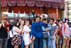 De vreemdelingen wachten uit de regen dichtbij de Centrale opslag van Moskou stock foto