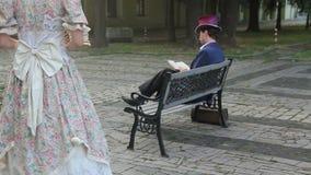 De vreemdere vrouw ging zitten op een bank aan de man stock video