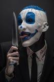 De vreselijke clown en Halloween als thema hebben: De gekke blauwe clown in een zwart kostuum met een mes in zijn hand isoleerde  Royalty-vrije Stock Afbeeldingen