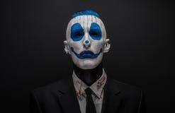 De vreselijke clown en Halloween als thema hebben: Gekke blauwe clown in zwart die kostuum op een donkere achtergrond in de studi Royalty-vrije Stock Afbeelding