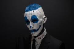 De vreselijke clown en Halloween als thema hebben: Gekke blauwe clown in zwart die kostuum op een donkere achtergrond in de studi royalty-vrije stock afbeeldingen