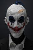 De vreselijke clown en Halloween als thema hebben: Gekke vreselijke blauwe clown in zwart die kostuum op een donkere achtergrond  Royalty-vrije Stock Afbeeldingen