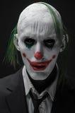 De vreselijke clown en Halloween als thema hebben: Gekke vreselijke groene clown in zwart die kostuum op een donkere achtergrond  royalty-vrije stock foto