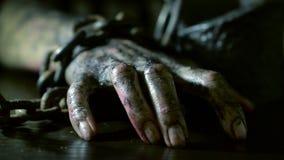 De vreselijke gebrande hand wordt geketend aan een ijzerketting monsterhand op Halloween stock video