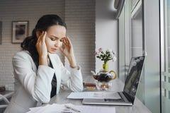De vreselijke hoofdpijn maakt vrouw tijdens werkdag lijden Stock Foto