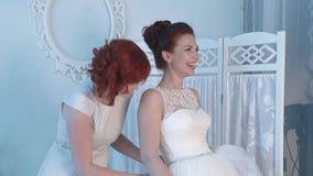 De vriend van de bruid helpt de bruidslijtage een huwelijkskleding, lachen zij, dan de bruiddalingen stock video