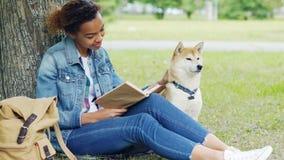 De vriendelijke gemengde rasvrouw leest boek in park en strijkt samen haar hondzitting op gazon onder boom intelligent stock videobeelden