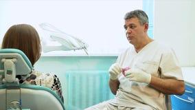 De vriendelijke man de tandarts spreekt in een licht bureau aan de patiënt stock footage