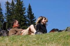 De vrienden bevinden zich in gras op berg stock foto