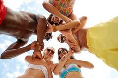 De vrienden die aan elkaar houden overhandigen op de zomerstrand royalty-vrije stock afbeelding