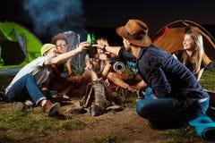 De vrienden die dichtbij vuur, het drinken zitten dragen, het glimlachen, het spreken, het rusten camping royalty-vrije stock fotografie