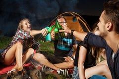 De vrienden die dichtbij vuur, het drinken zitten dragen, het glimlachen, het spreken, het rusten camping stock afbeelding